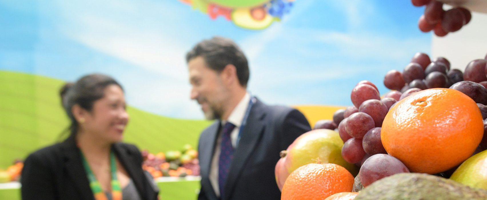 Branding voor associaties: foto van 2 medewerkers van Fruit associatie in zonnige en landelijke omgeving met fruit op de voorgrond.